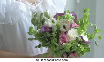 Blond girl in white dress with charming bouquet of flowers, smelling, slow motion