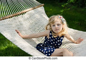 blond girl in white hammock