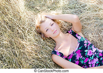 Blond girl is lying on haystack in summer sunny day