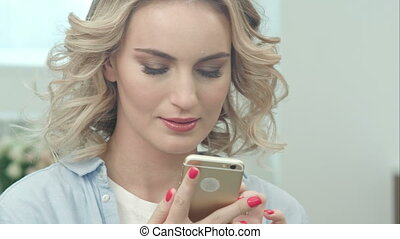 Blond girl is sitting in a living room and looking at smartphone screen smiling