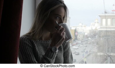 Blond girl is sitting on the window sill