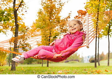 Blond girl laying on net of hammock in park