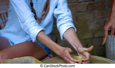 blond girl learns to make clay pot in pottery workshop
