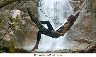 Blond Girl Lies in Hammock against Foamy Waterfall - blonde...