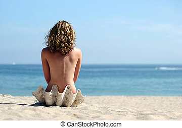 Blond girl on beach - A girl sitting in sea shell on the...