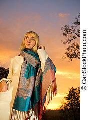 Blond girl on sunset sky background