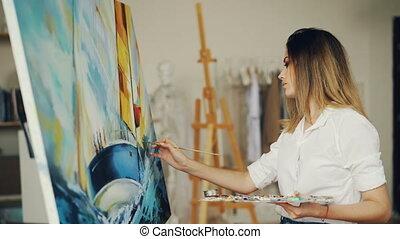 Blond girl painter is working in studio depicting sea...