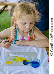 blond girl painting into t-shirt
