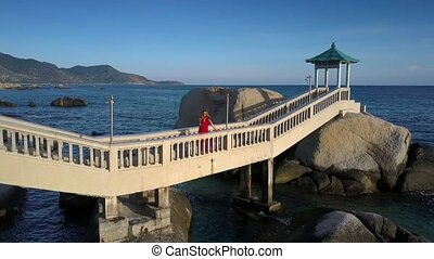 Blond Girl Poses on Bridge against Azure Ocean Upper View