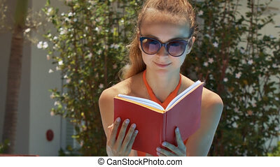 Blond Girl Reads Red Book by Tropical Plant Close View -...