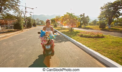 Blond Girl Rides Motorbike along Empty Street