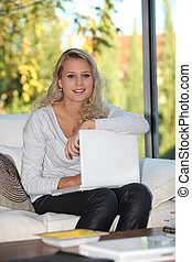 Blond girl sat at home with laptop computer