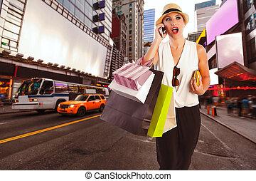 Blond girl shopaholic talking phone Times Square