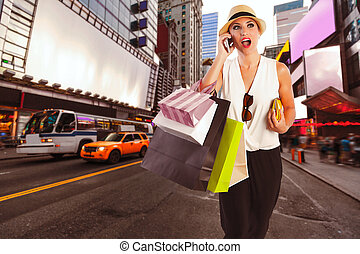 Blond girl shopaholic talking phone Times Square