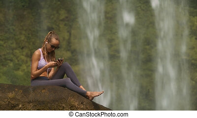 Blond Girl Sits Barefoot on Stone Listens to Music - close...