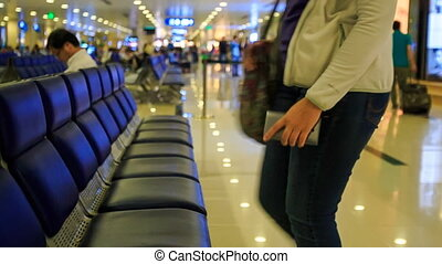 Blond Girl Sits down on Waiting Bench in Airport Terminal -...