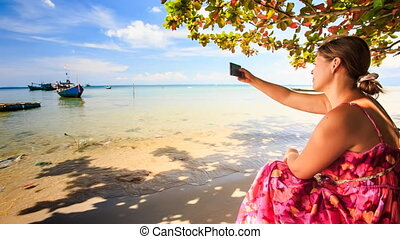 Blond Girl Sits on Beach Takes Photo of Boats in Azure Sea