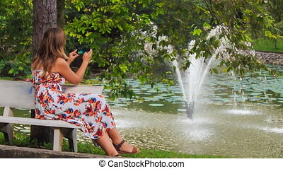 Blond Girl Sits on Bench at Fountain Takes Photos with...