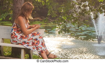 Blond Girl Sits on Bench at Pond Takes Photo with Iphone in...