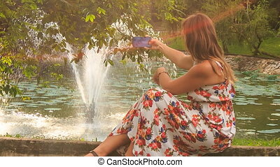 Blond Girl Sits on Fountain Barrier Makes Selfie with Iphone...