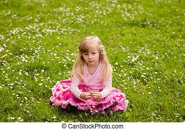 blond girl sitting in meadow