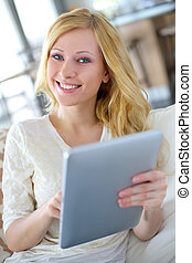 Blond girl sitting in sofa with digital tablet