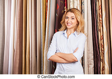 blond girl standing in fabric store. beautiful lady selling...