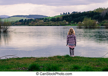 girl standing in the waterside of pond