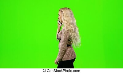 Blond girl talking on the phone. Green screen. Side view