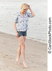 blond girl walking along lake shore. beautiful woman walking barefoot on sand
