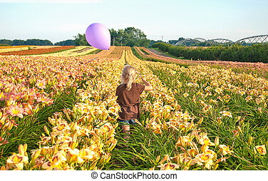 blond girl with balloon in lily field