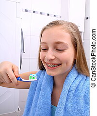 Blond girl with braces smiling while brushing your teeth