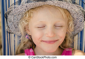 blond girl with hat and closed eyes portrait