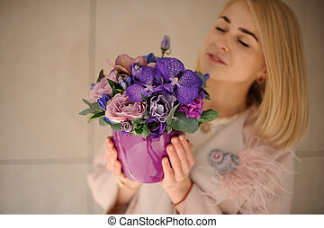 Blond girl with irises in flower pot