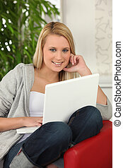 Blond girl with laptop computer sitting on a sofa