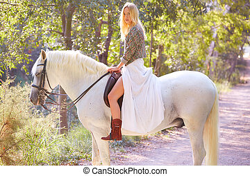 Blond girl woman riding a white horse in track