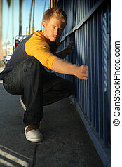 blond guy by fence