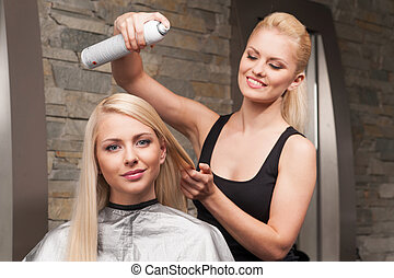 blond hairdresser applying spray on client's hair. Female hairdresser works on woman hair in salon