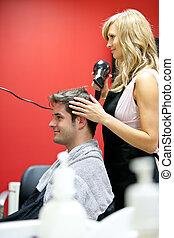 Blond hairdresser drying her customer's hair