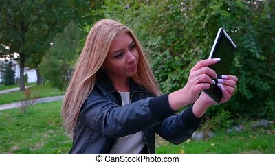 Blond haired girl is making selfie using her tablet PC and after she is sending it somewere to social net