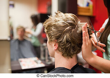Blond-haired man having a haircut with scissors