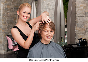 blond hairstylist applying hair mousse spray. young attractive man sitting in hair salon