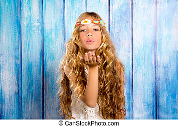 Blond hippie children girl blowing mouth with hand on blue...