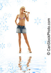 blond in denim skirt and bikini on white sand