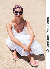 Blond in white dress on a beach