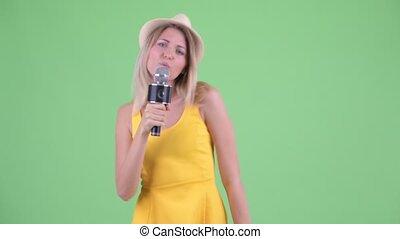 blond, jeune, touriste, chant, femme heureuse, microphone