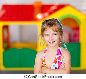 blond kid girl crossed arms in toy house playground