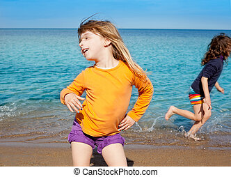 Blond kid girl dancing at the beach and friend run