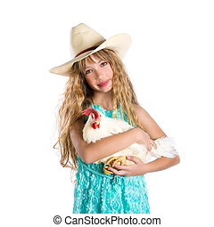 Blond kid girl farmer holding white hen on arms with cowboy...