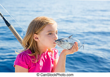 Blond kid girl fishing tuna little tunny kissing for release